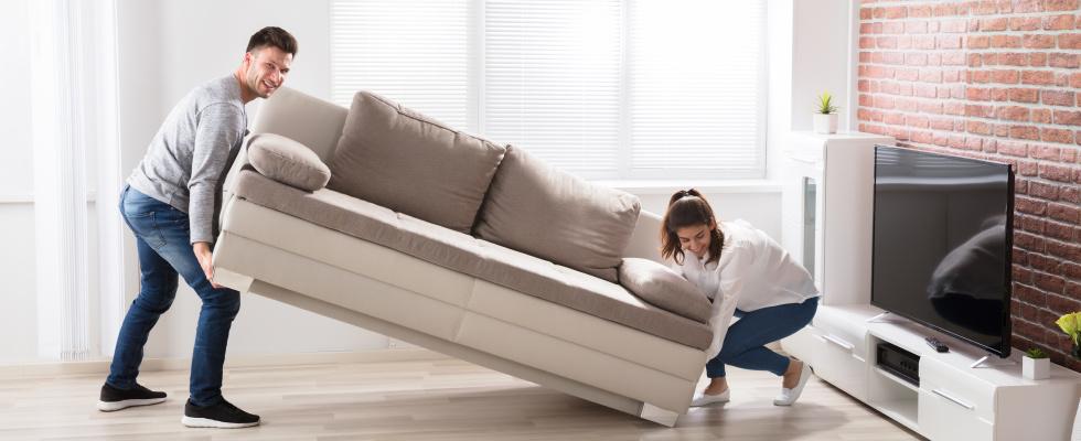 Frau und Mann heben Sofa