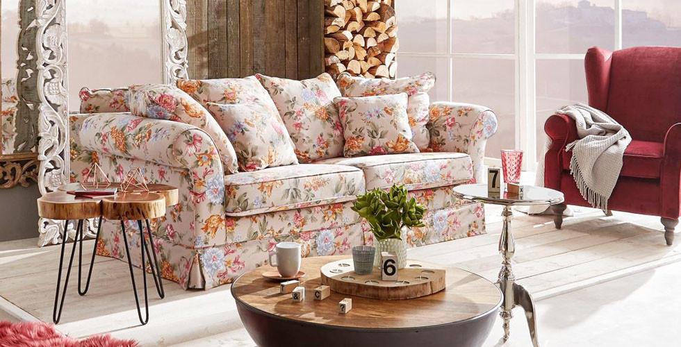 Příjemná 3místná pohovka ve venkovském stylu, s květinovým látkovým potahem a spoustou dekoračních polštářů, v XXXLutz.
