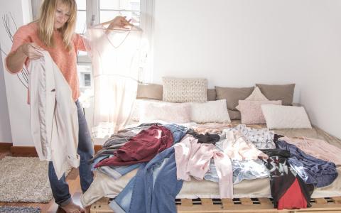 Frau sortiert Klamotten aus Kleider liegen auf dem Bett