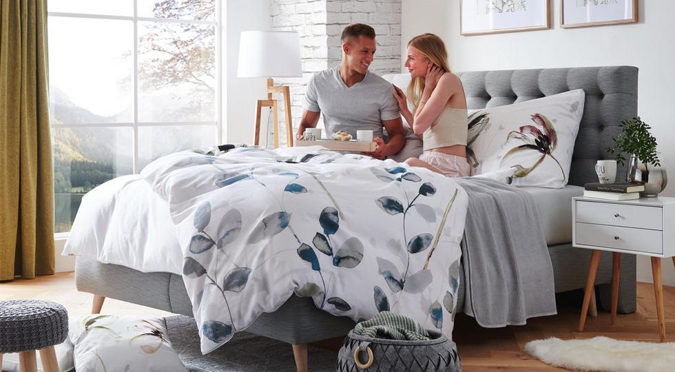 Pärchen im Polsterbett mit weißer Bettwäsche