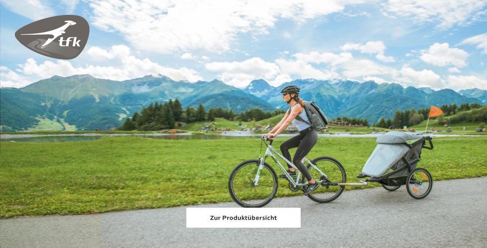 Frau mit Fahrrad und TFK Anhänger für Kleinkinder