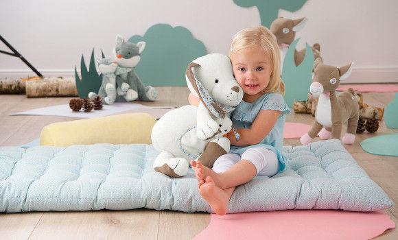 Kleinkind auf einer Spieldecke mit Kuscheltier