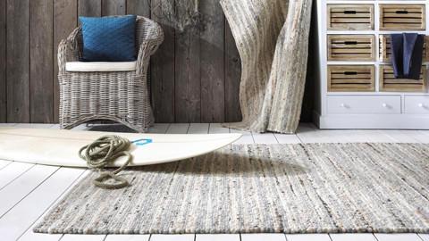 ručně tkaný koberec přírodní barva ratanové křeslo modrý polštář