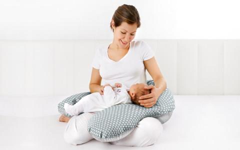 Mutter mit Baby auf Stillkissen