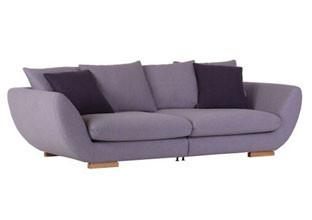 Velká pohovka s látkovým potahem fialové barvy a lila polštáři v XXXLutz.