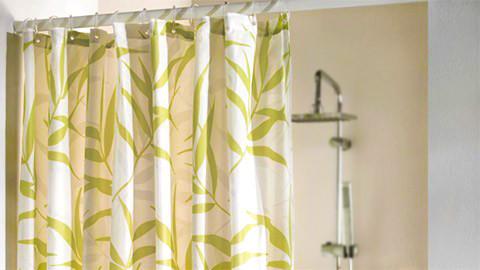 Bílý závěs do sprchy se zelenými listy.