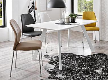 bijeli stol i stolice u različitim bojama