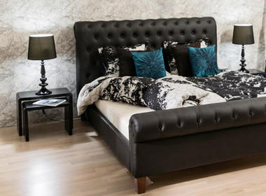 Visoka postelja v črni barvi, z modno dekoracijo