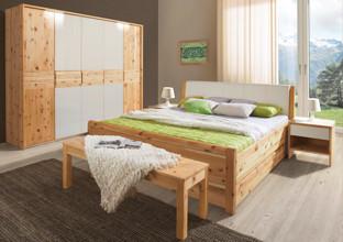 Ložnice ze dřeva borovice s dekou a polštářem v zelené.