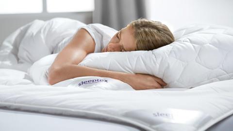 Blonde Frau auf Kopfpolster im Bett.