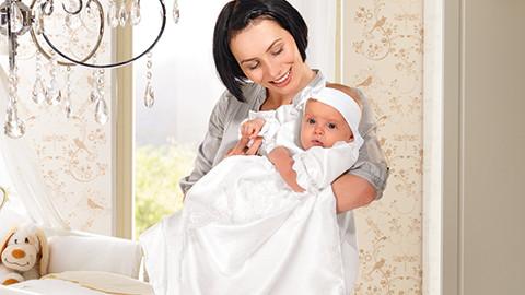 Mutter mit Kind im Taufkleid weiß