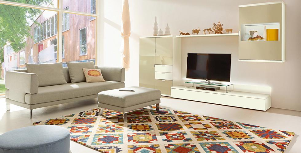 Moderne Wohnzimmermöbel in hellen Farben mit buntem Teppich