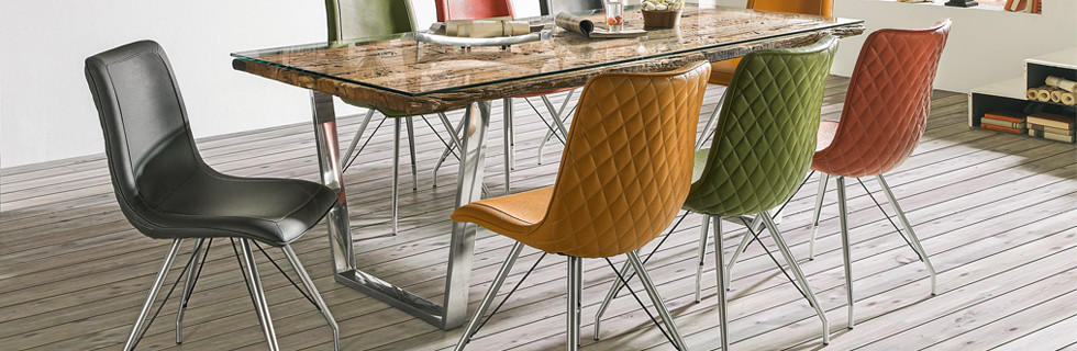 Stoli iz pisane mehke tkanine ob jedilni mizi, ki je kombinirana s steklom, lesom in kovino.