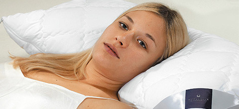 Nackenstütze mit Frau im Bett.