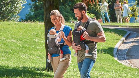 Eltern mit Babytragen grau schwarz im Park